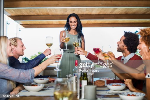 Hosting A Dinner Party woman hosting a dinner party stock photo | getty images