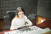 Beautiful young woman with clipboard hosting show live on radio station, sitting in front of sounds mixed console and microphone