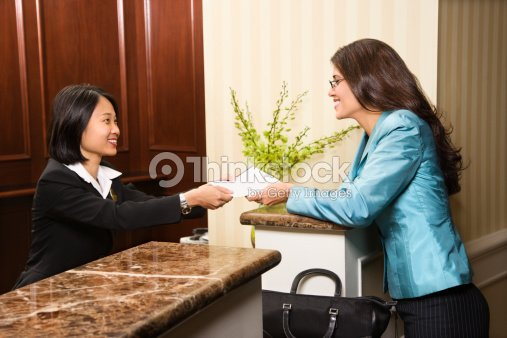 Woman Hotel Desk Clerk Handing Paperwork To Guest Stock Photo