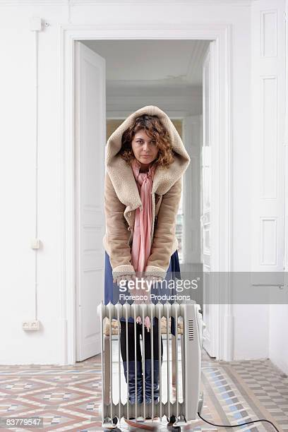 Woman huddled by radiator