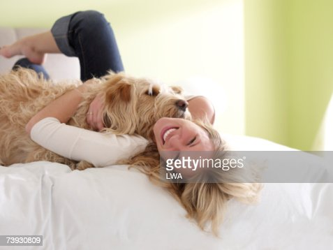 Woman hugging dog, lying on bed : Stock Photo