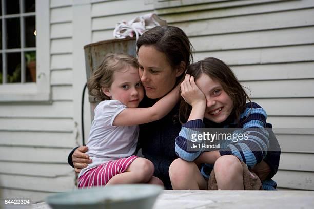 Femme embrassant filles à l'extérieur de la maison de ferme
