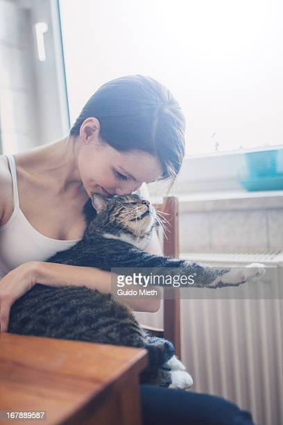 Woman hugging her cat in kitchen.