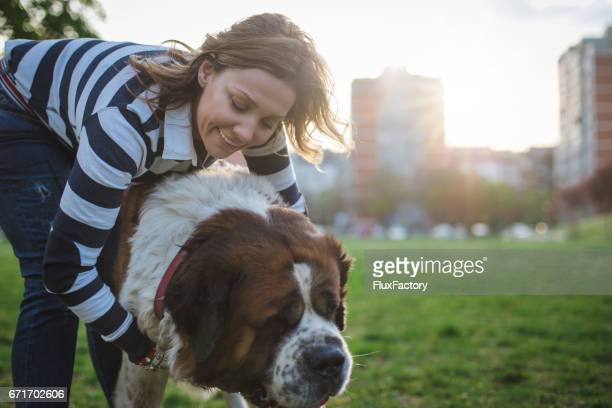 A woman hugging her St.Bernard dog in the park