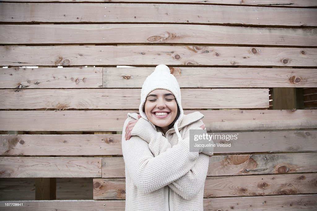 Woman hugging herself in front of wooden structure : Stock Photo