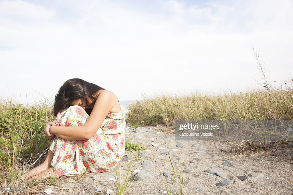 Woman hugging herself on beach : Stock Photo