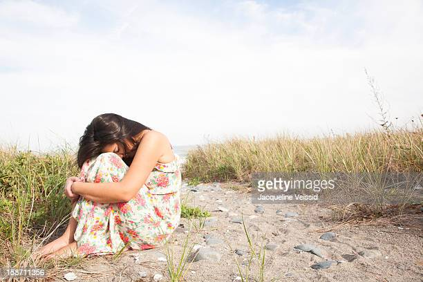 Woman hugging herself on beach