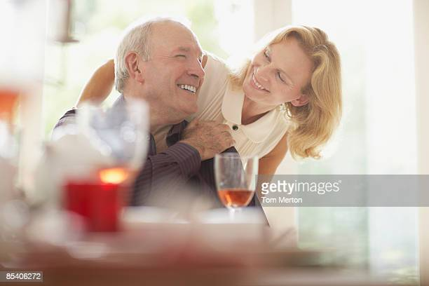 Woman hugging husband at dinner table
