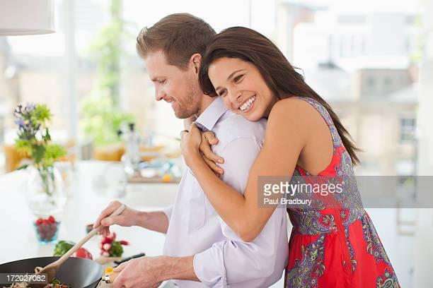 Femme embrassant son mari pendant qu'il sert des plats dans la cuisine