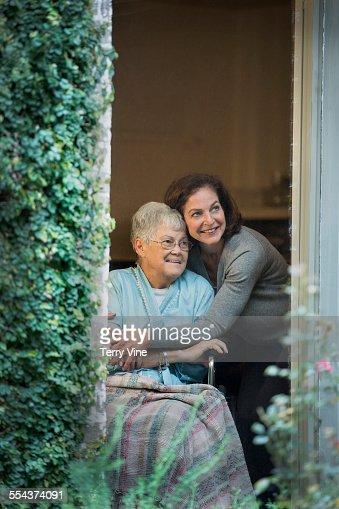 Woman hugging mother in wheelchair near window : Stock Photo