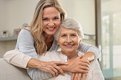 Cheerful mature woman embracing senior mother at home and looking at camera. Portrait of elderly mother and middle aged daughter smiling together. Happy daughter embracing from behind elderly mom sitt