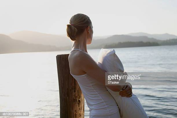 Woman hugging pillow and looking at lake