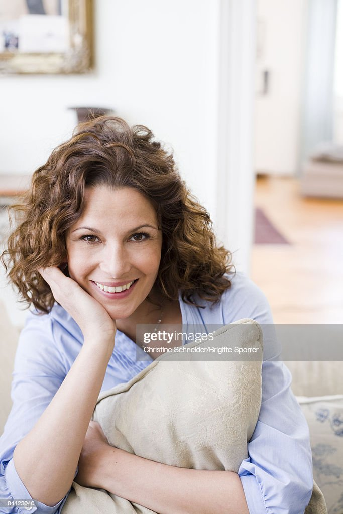 Woman hugging pillow sitting on a couch : Stock Photo