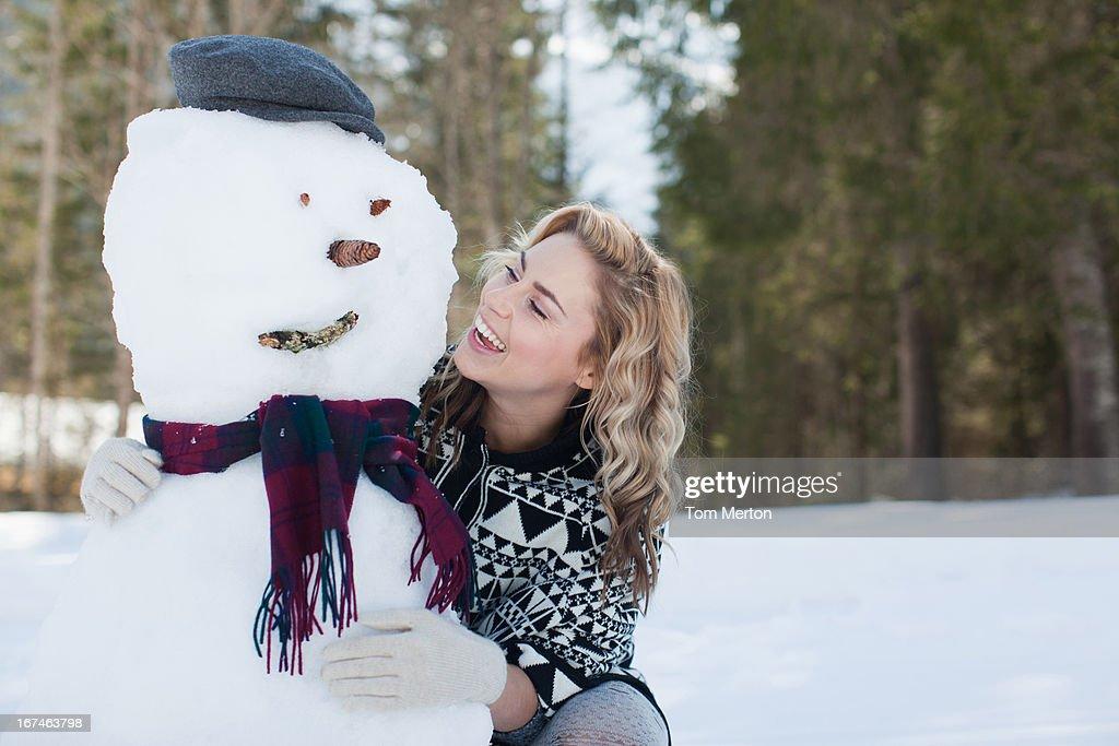 Woman hugging snowman : Stock Photo