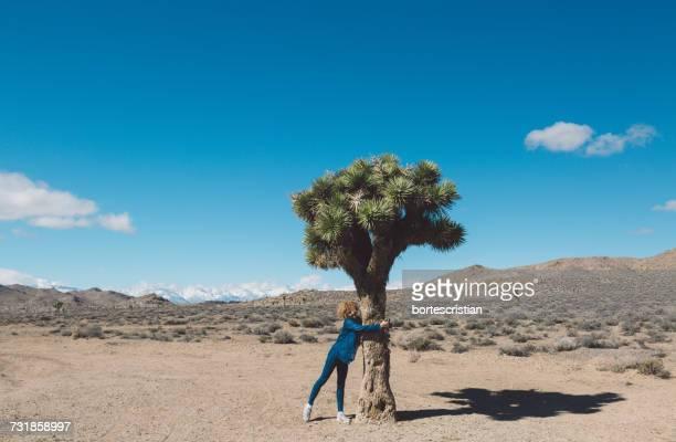 Woman Hugging Tree In Desert Against Blue Sky