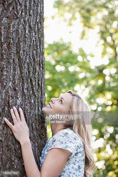 Frau umarmen Baum im Freien