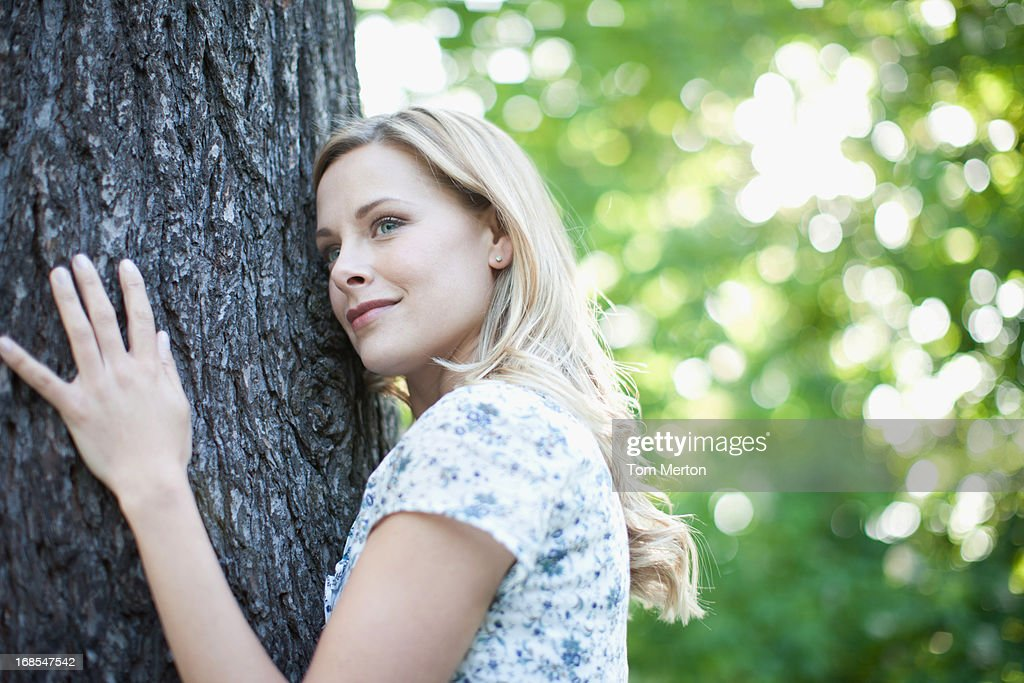 Woman hugging tree outdoors : Stock Photo