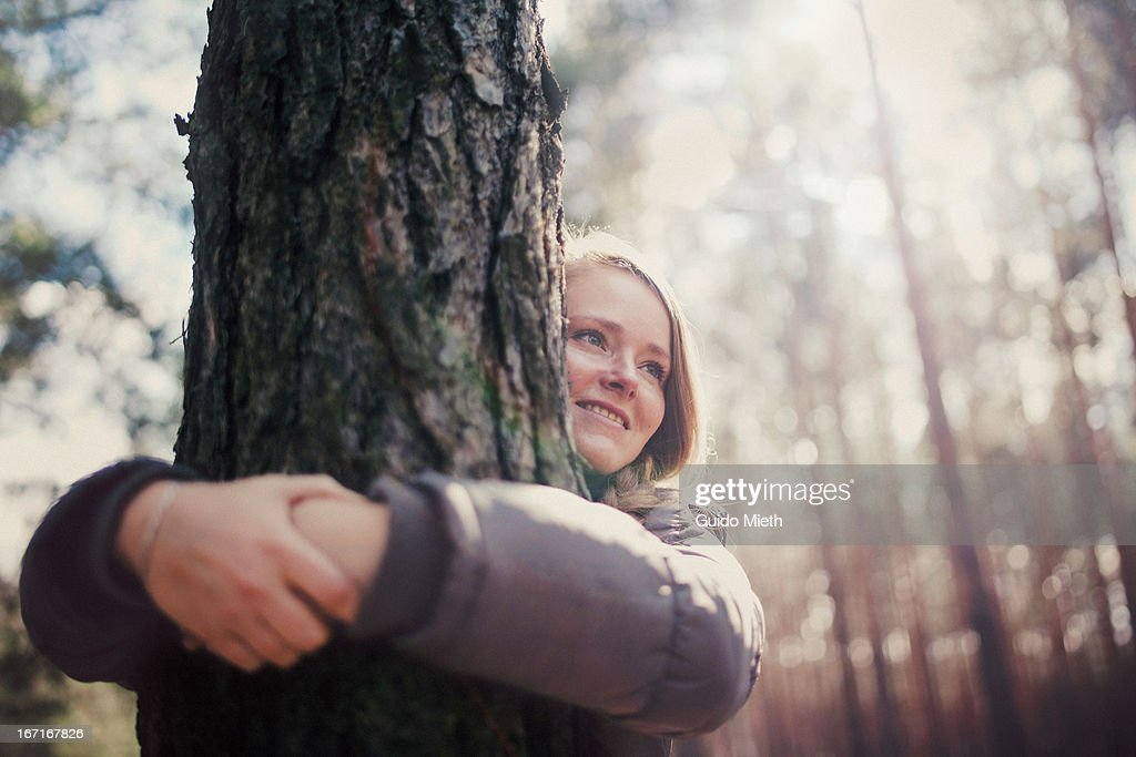 Woman  hugging tree, smiling. : Stock Photo
