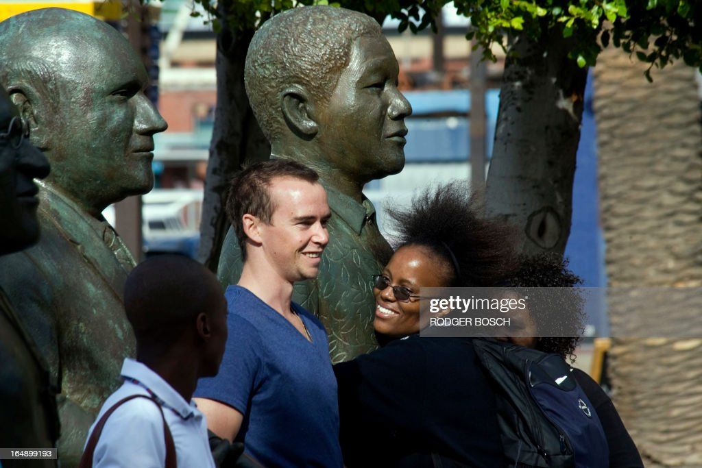 A woman hugs a bronze statue representing former South African President Nelson Mandela, while other people get their pictures taken with the statues of South Africa's four Nobel Peace Prize winners (Chief Albert Luthuli, Archbishop Desmond Tutu, F.W. De Klerk, and Mandela) in Cape Town on March 29, 2013. Mandela was spending a second day in hospital after responding positively to treatment for a lung infection, the latest health scare for the revered anti-apartheid icon.