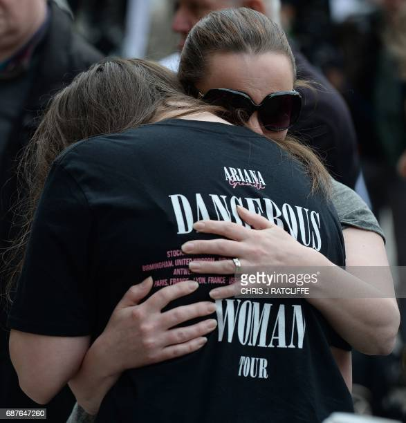 A woman hugs a girl wearing a tshirt from Ariana Grande's Dangerous Woman near floral tributes in Albert Square in Manchester northwest England on...