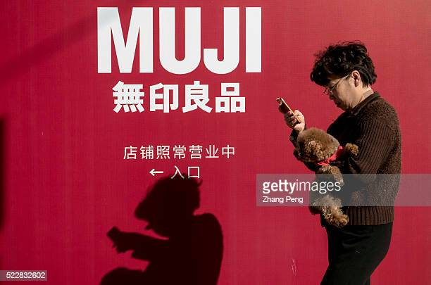A woman hugs a pet dog while looking at her mobile phone as she walks past MUJI Shanghai Huaihai 755 a flagship store located at Huaihai road MUJI...