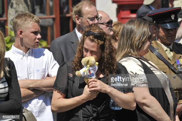 A woman hugs a teddy bear as mourners line the streets of Wootton Bassett when the body Lance Corporal Kieron Hill passes through the town after...