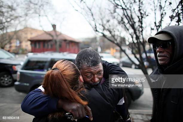 A woman hugs Ben Carr stepfather of Eric Garner as she walks by Garner's memorial in Staten Island NY on December 05 2014 Garner died in July after a...