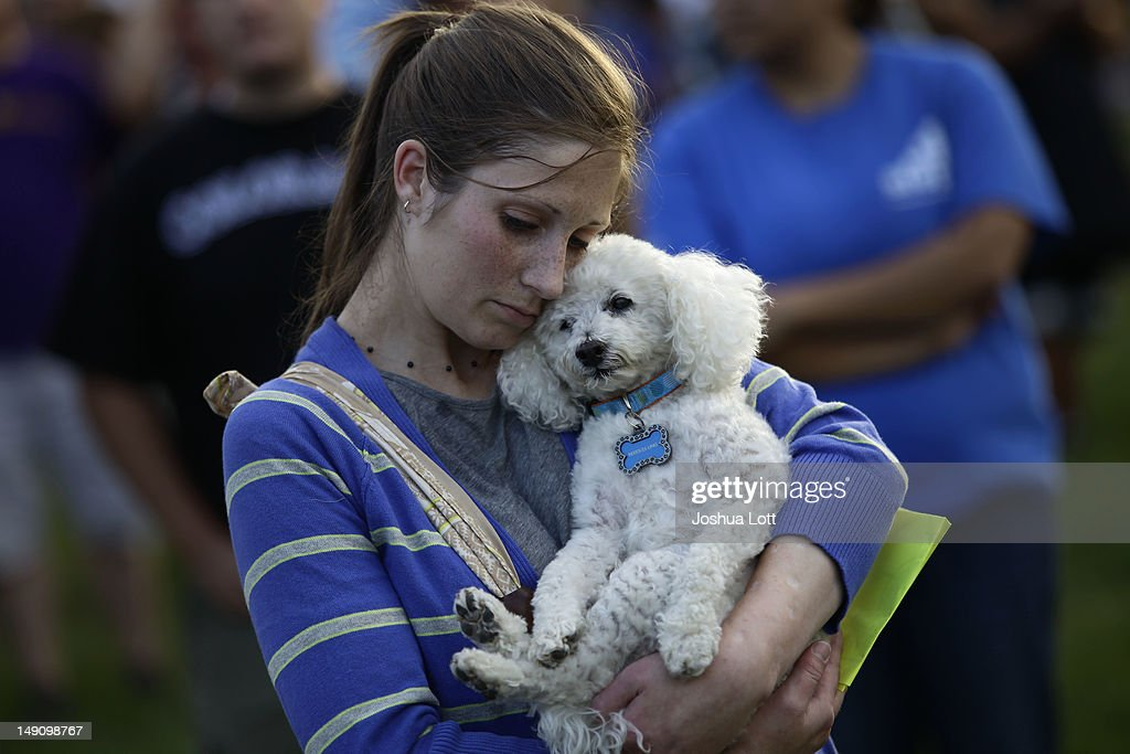 A woman hugs her dog during a memorial outside the Aurora Municipal Center July 22, 2012 in Aurora, Colorado. The memorial was for the victims that were killed and wounded during the mass shooting at a movie theater last Friday. James Eagan Holmes, 24, is accused of killing 12 people at a screening of the new 'Batman' film.