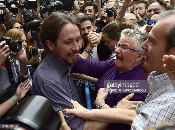 A woman hugs leader of 'Podemos' Pablo Iglesias as they celebrate the investiture of Manuela Carmena as new mayor of Madrid at the Cibeles Palace...