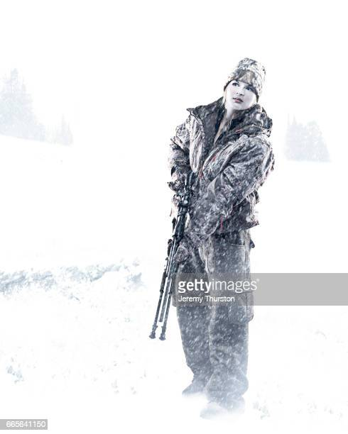Woman hunting in snowstorm wearing camouflage