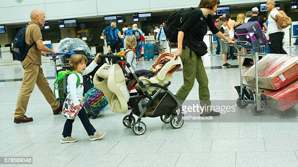 Woman hurry with luggage, baby buggy and kids