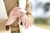 Close up of a woman hydrating hands with moisturizer cream in winter with a snowy mountain in the background