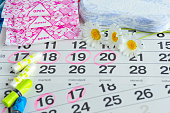 Woman hygiene protection , calendar close up.menstruation with cotton swabs , white daisies, Sanitary napkins on a light background