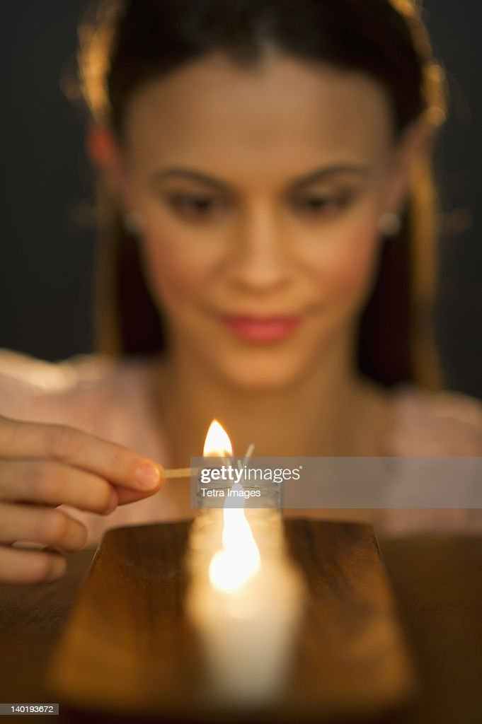 Woman igniting candle