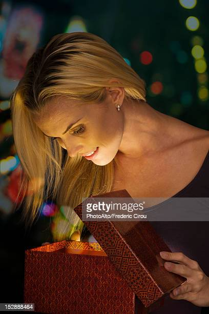Woman illuminated by golden light as she opens Christmas gift