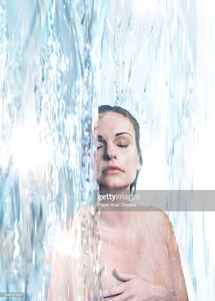 Woman immersed in a waterfall : Stock Photo