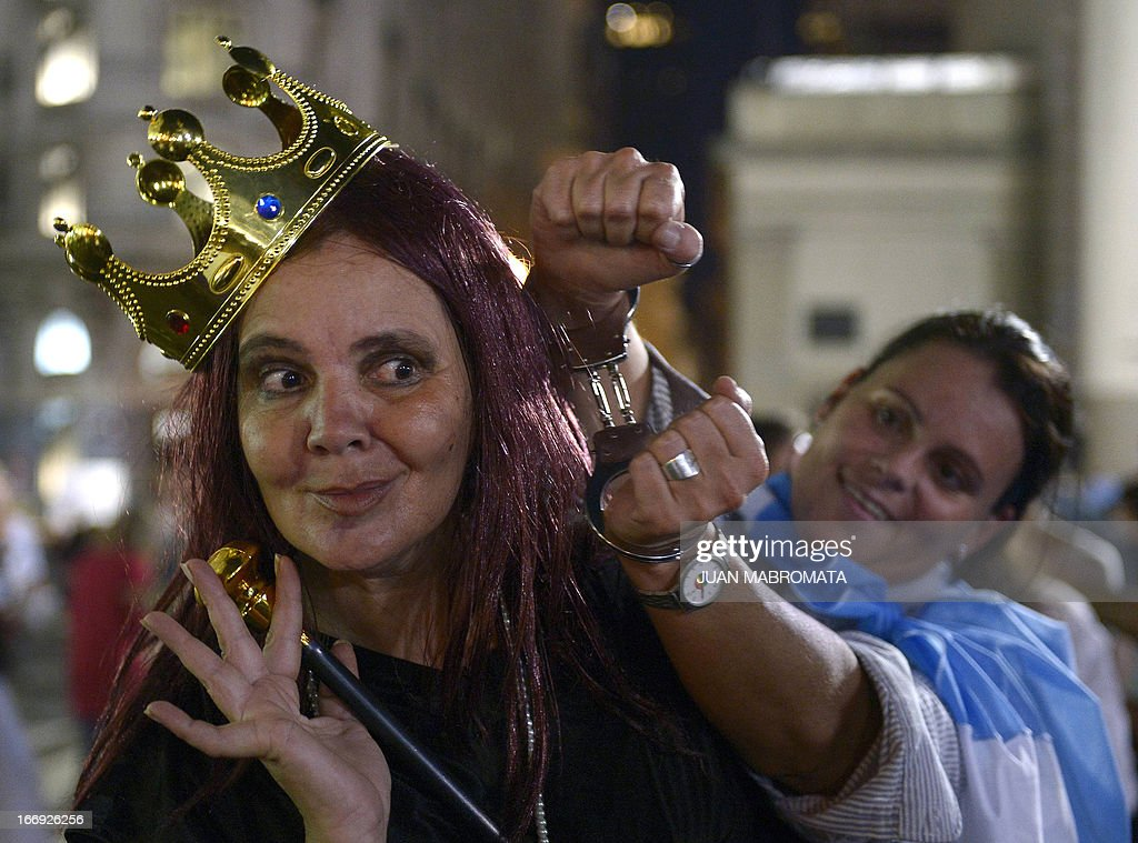 A woman impersonating Argentina's President Cristina Fernandez de Kirchner as a queen poses next to another woman handcuffed in Plaza de Mayo square, in front of the government palace during a 'cacerolazo' (a form of civilian protest where saucepans are used to make noise) Mrs.Kirchner's government policies in Buenos Aires on April 18, 2013.
