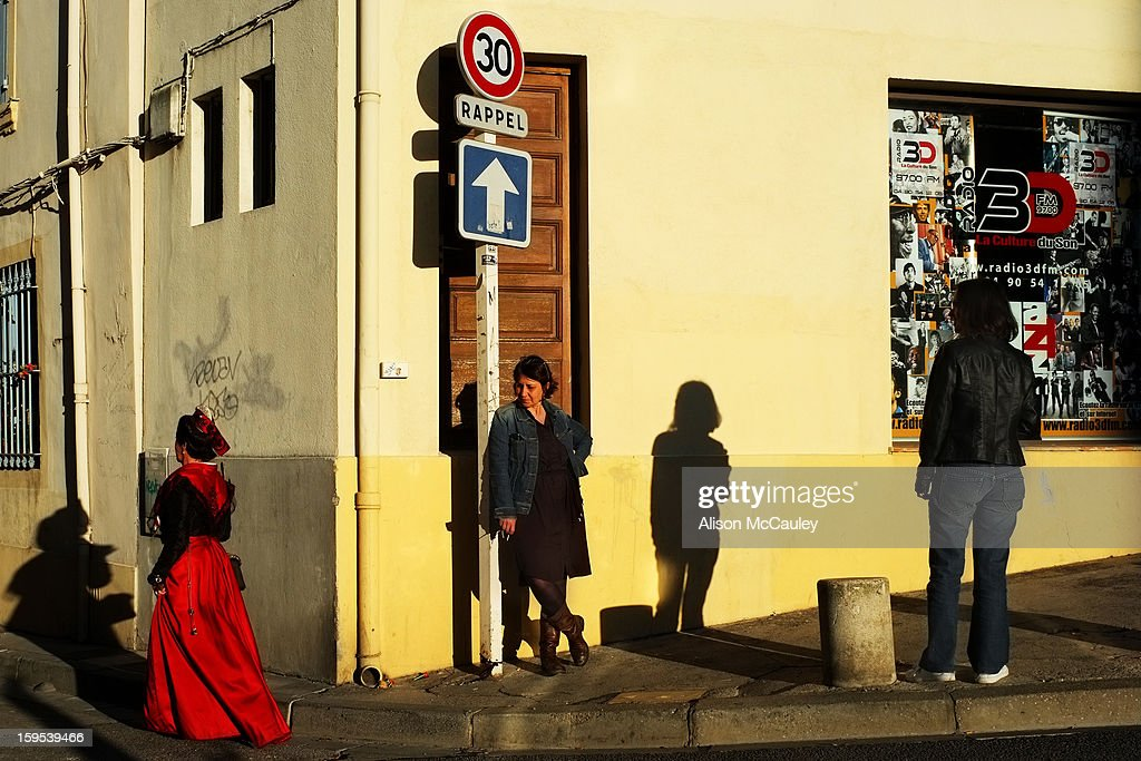 CONTENT] A woman in 19th century costume walks past a street corner. Another woman, dressed normally, looks on curiously as she leans against a sign post. The late afternoon light is golden and the shadows are deep.