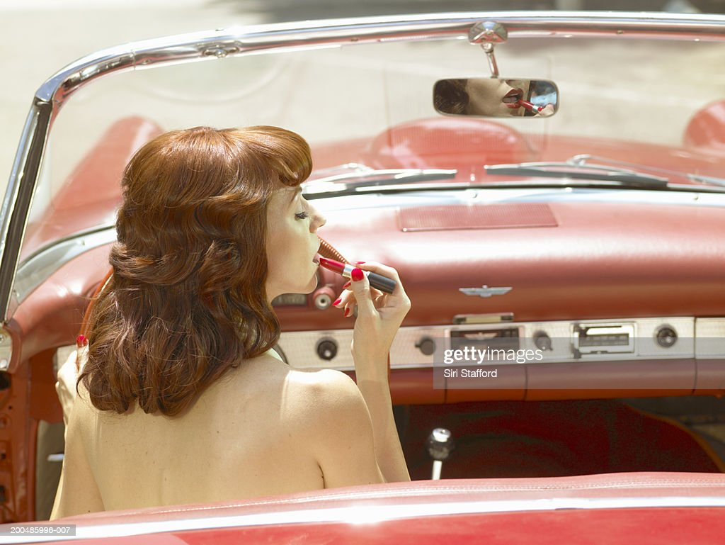 Woman in 50's style dress  putting on lipstick in vintage car : Stock Photo