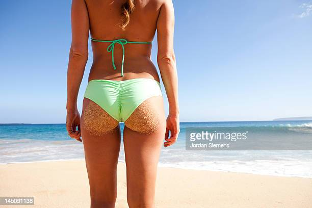Woman in a bathing suite wth a sandy butt.