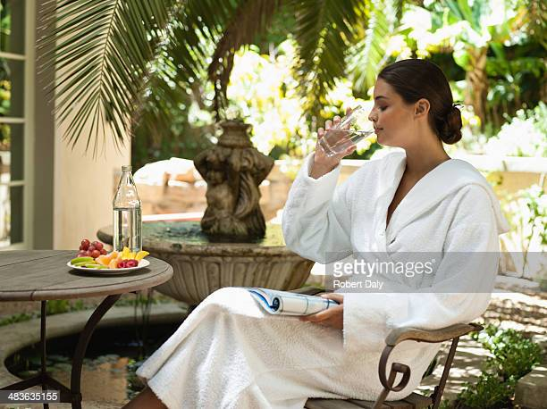 Woman in a bathrobe drinking water and reading a magazine