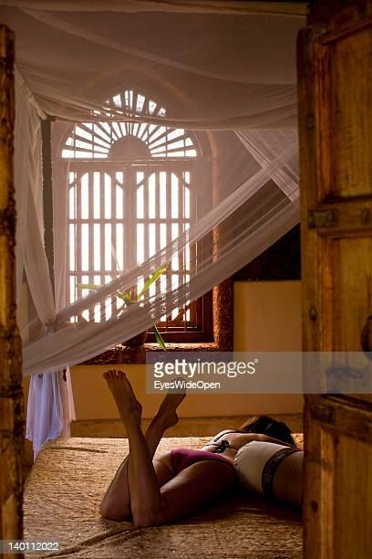 A woman in a bikini lies in bed taking a nap in the maharaja suite of Yoga Magic Eco Retreat in Anjuna on February 1 2012 in Goa India