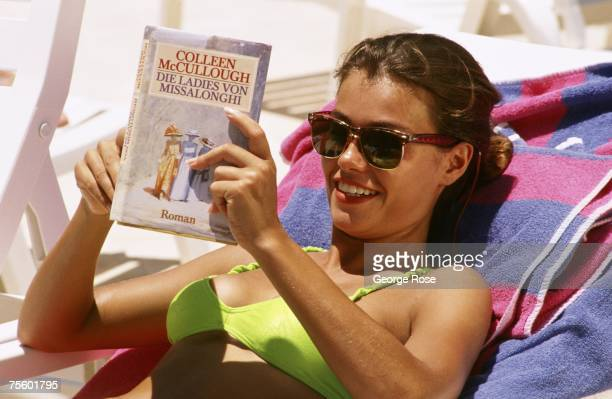A woman in a bikini reads a book while sunbathing next to a resort pool in this 1989 Cancun Mexico photo