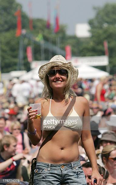 A woman in a bikini top and denim shorts drinking Pimms Isle of Wight Festival June 2007