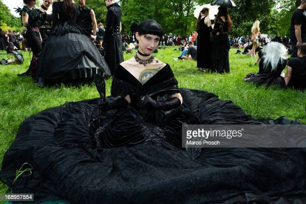 A woman in a black dress sits on the lawn during the traditional park picnic on the first day of the annual WaveGotik Treffen or Wave and Goth...