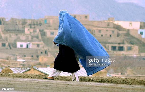 A woman in a burka makes her way towards her home in Kabul 02 March 2003 Millions of Afghan women were forced by the former Islamic hardline Taliban...