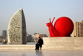 A woman in a burka sits by a sculpture of a snail near the Heydar Aliyev Cultural Center ahead of the 1st European Games on June 11 2015 in Baku...