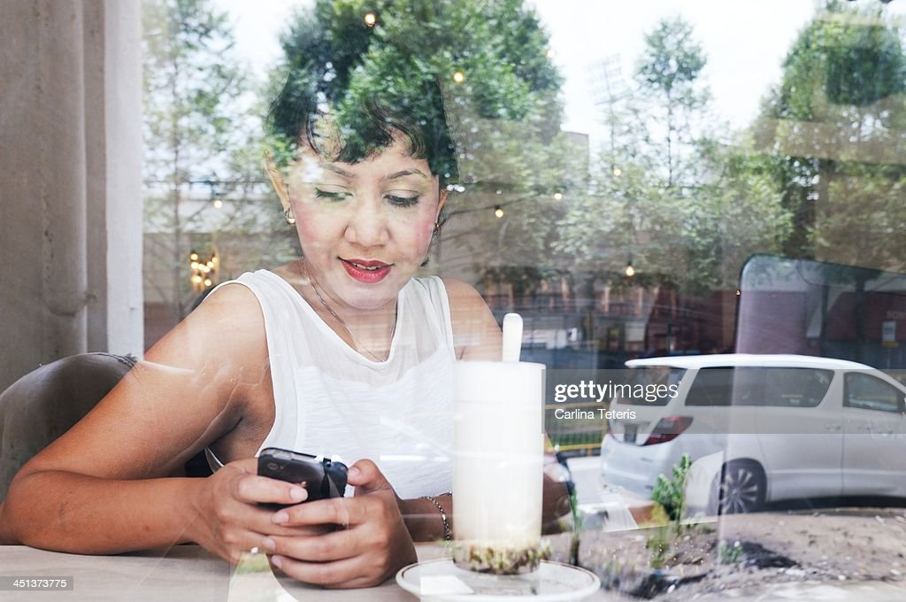 Woman in a cafe on smart phone : Stock Photo