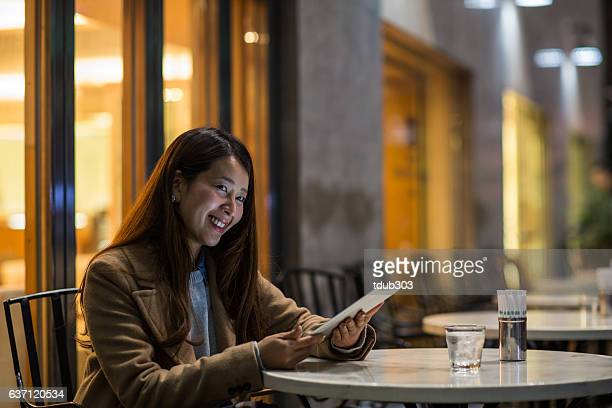 Woman in a cafe using a digital tablet at night