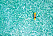 Woman in a canoe over turquoise, tropical waters in the Maldives